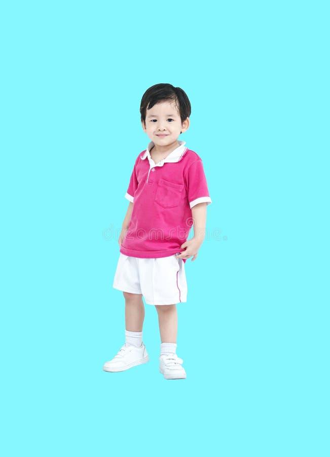 Zbliżenie azjatykcia chłopiec w sport odzieży mundurze odizolowywającym na błękitnym tle obraz royalty free