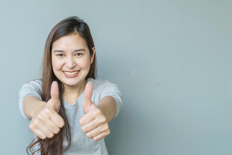 Zbliżenie azjatykcia kobieta z podziwia ruch z uśmiech twarzą na zamazana ściana textured cementu tle z kopii przestrzenią obraz stock