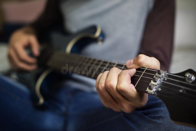 Zbliżenie bawić się gitarę nastoletni chłopak obraz stock