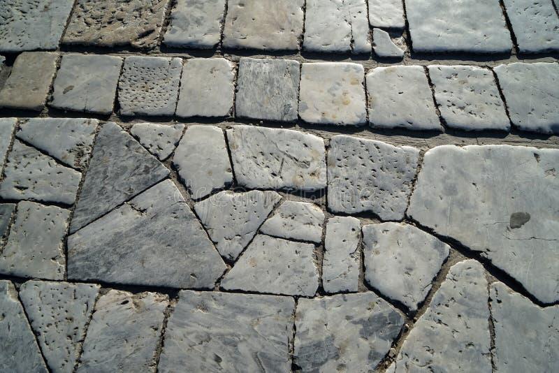 Zbliżenie białej i popielatej kolor cegły marmuru kamienia tekstury plenerowy bruk w naturalnym cięcie wzoru tle pod światłem sło zdjęcia royalty free