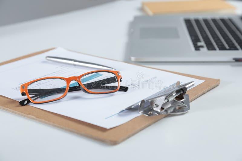 Zbliżenie biały desktop z laptopem, szkłami, filiżanką, notepads i innymi rzeczami na rozmytym miasta tle, obraz stock