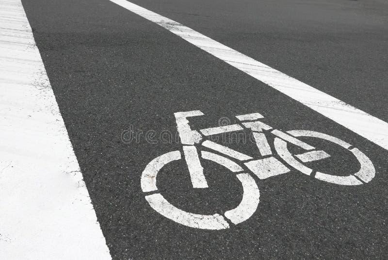 Zbliżenie biały rowerowy symbol jest na samochodowej drodze zdjęcie stock