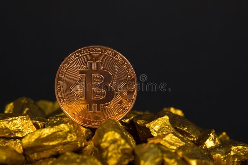 Zbliżenie bitcoin cyfrowa waluta i kruszec na złocistej bryłki lub złota czarnym tle, cennym kamieniu lub gomółce złoty kamień, obraz stock