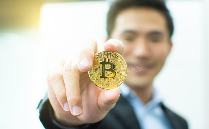 Zbliżenie bitcoin z defocused biznesowym mężczyzną obraz royalty free
