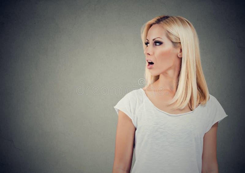 Zbliżenie bocznego widoku profilu portreta kobieta opowiada z otwartym usta zdjęcia royalty free