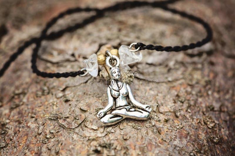 Zbliżenie bransoletka z joga dziewczyną w lotosowej pozyci fotografia stock