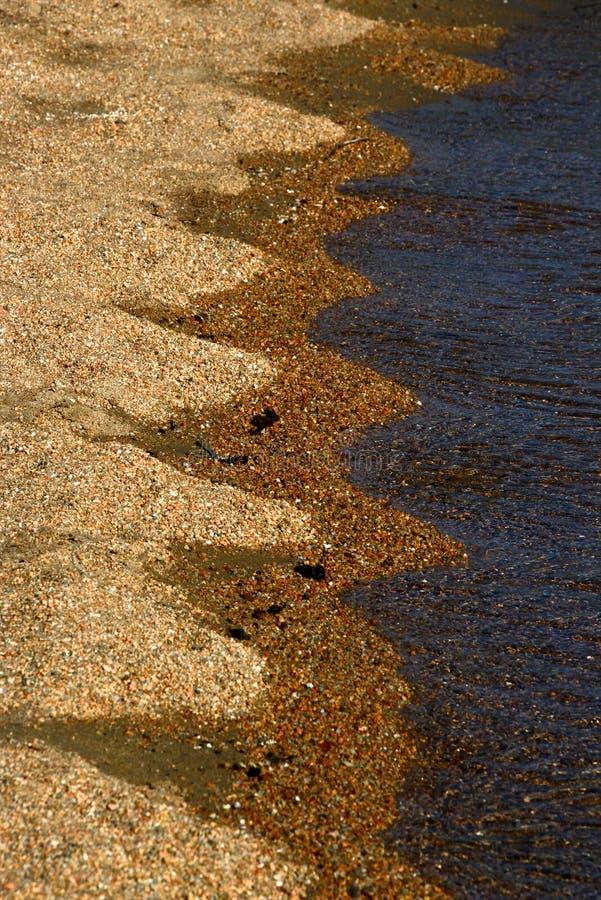 Zbliżenie brzeg z wodą na piaskowatej plaży która tworzy krzywy i kształty obrazy royalty free