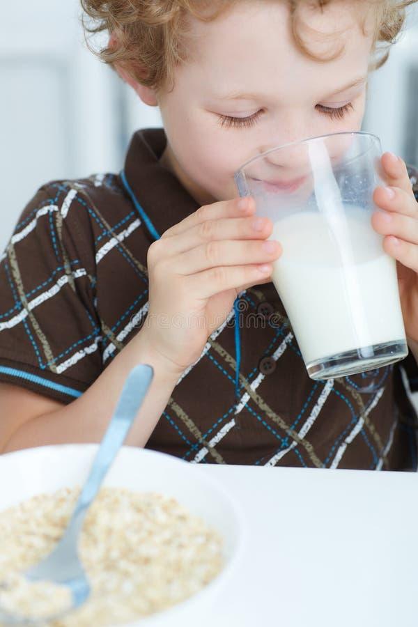 Zbliżenie chłopiec Kaukaski pić dojny i uśmiechnięty podczas gdy mieć śniadanie w kuchni zdjęcie royalty free