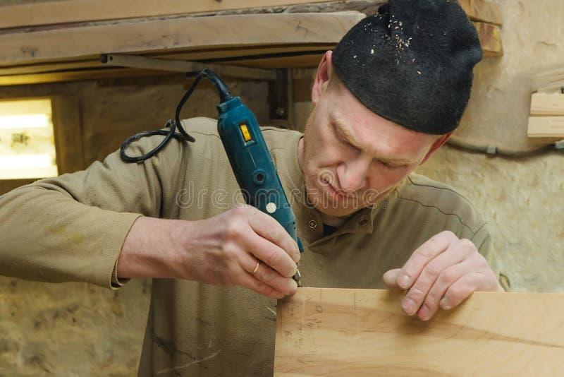 Zbliżenie cieśla w nakrętki i puloweru Sanding desce w warsztacie Przemysłowy Manufactoring pojęcie zdjęcie stock