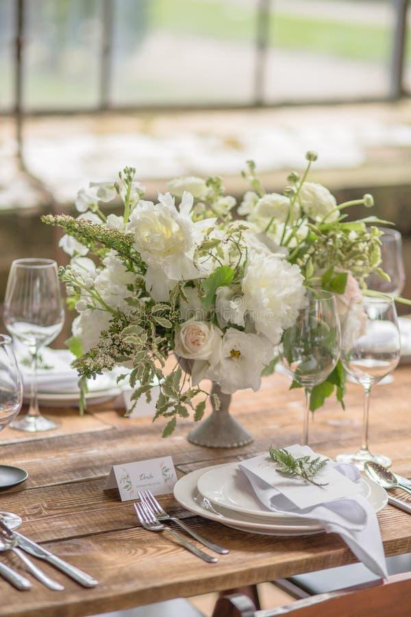Zbliżenie dekoracja ślubny stół z kwiatami w wieśniaka stylu dla gości przy przyjęciem urodzinowym lub ślubem zdjęcia stock