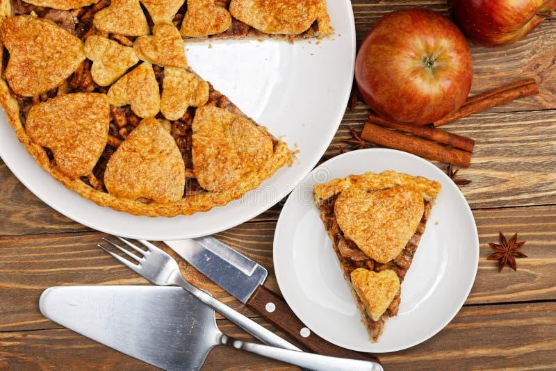 Zbliżenie domowej roboty jabłczany kulebiak z cynamonem i odcinającym kawałkiem na drewnianym stole zdjęcie stock