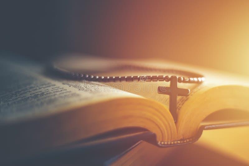 Zbliżenie drewniana chrześcijanina krzyża kolia obok świętej biblii fotografia stock