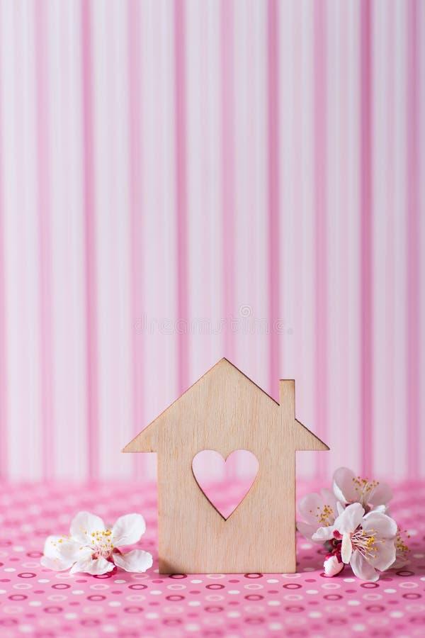 Zbliżenie drewniany dom z dziurą w formie otaczającej białymi kwiatonośnymi gałąź na menchiach serce paskował tło obrazy stock