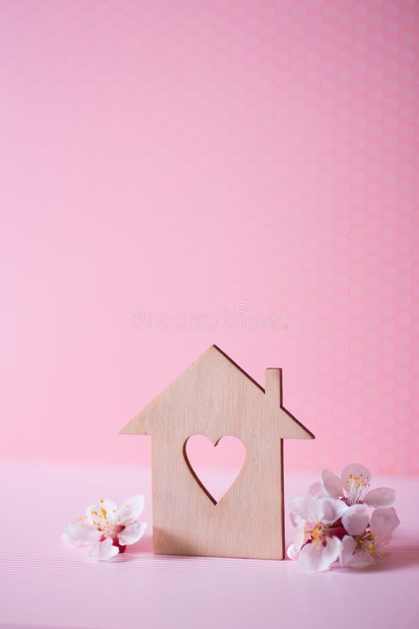 Zbliżenie drewniany dom z dziurą w formie otaczającej białymi kwiatonośnymi gałąź na pastelowych menchii tle serce zdjęcie royalty free