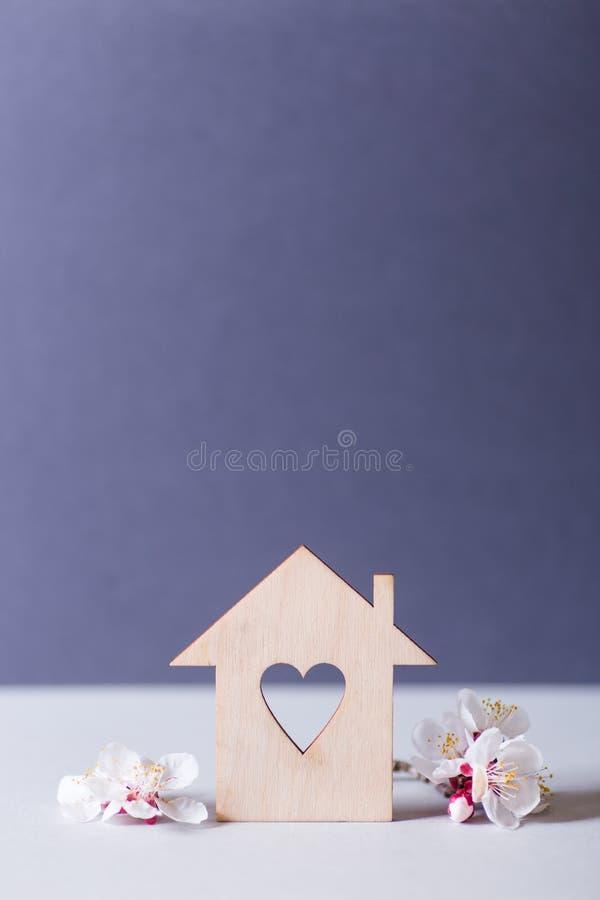 Zbliżenie drewniany dom z dziurą w formie otaczającej białymi kwiatonośnymi gałąź na szarym tle serce zdjęcie stock