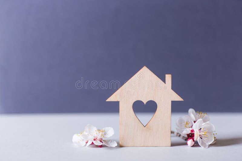 Zbliżenie drewniany dom z dziurą w formie otaczającej białymi kwiatonośnymi gałąź na szarym tle serce obrazy stock