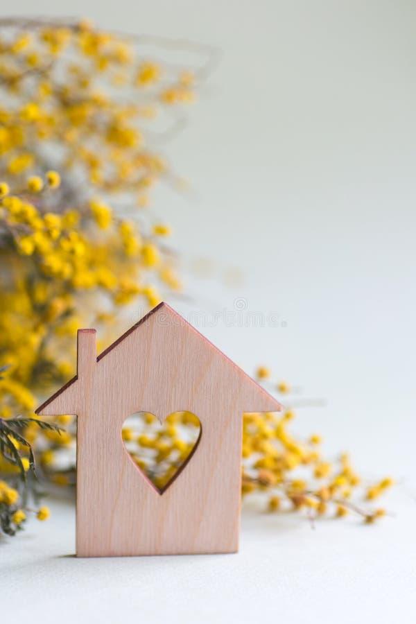 Zbliżenie drewniany dom z dziurą w formie serce z żółtą mimozą rozgałęzia się na lilym tle z kopii przestrzenią zdjęcia royalty free
