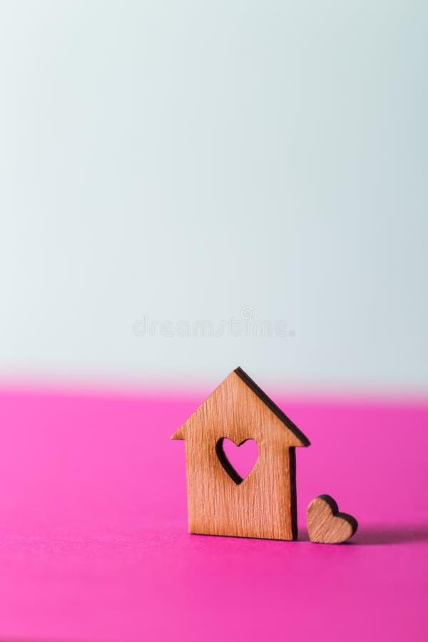 Zbliżenie drewniany dom z dziurą w formie serce na wibrującym dwubarwnym tle obraz stock