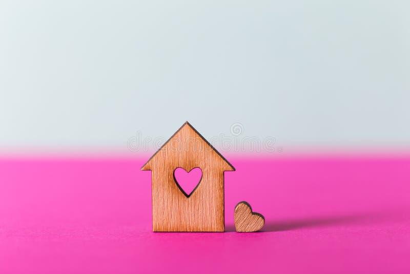 Zbliżenie drewniany dom z dziurą w formie serce na wibrującym dwubarwnym tle obraz royalty free