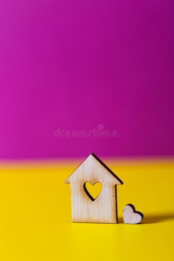 Zbliżenie drewniany dom z dziurą w formie serce na wibrującym karmazynów i koloru żółtego tle zdjęcie stock