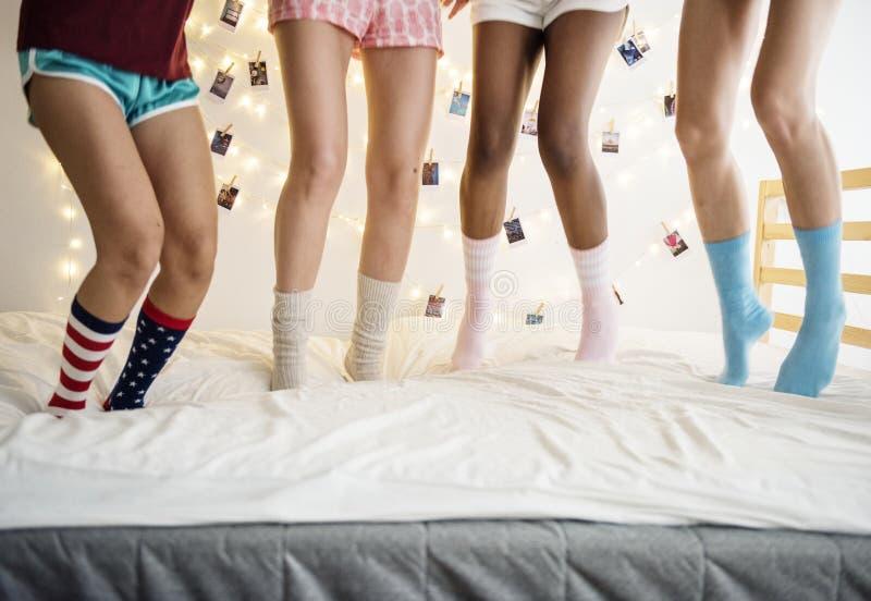 Zbliżenie dwa pary nogi z skarpetami skacze na łóżku zdjęcia stock