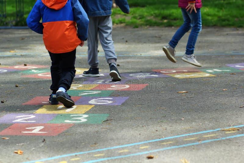 Zbliżenie dzieciaków cieki skacze hopscotch i bawić się przy szkołą fotografia stock