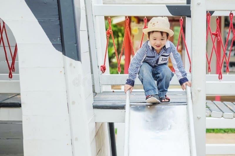 Zbliżenie dzieciaka azjatykcia sztuka suwak przy boiska tłem fotografia royalty free