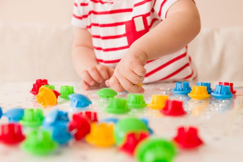 Zbliżenie dziecka ` s ręka bierze jaskrawą mozaikę rozdziela Bawić się kolor w domu i uczący się fotografia stock