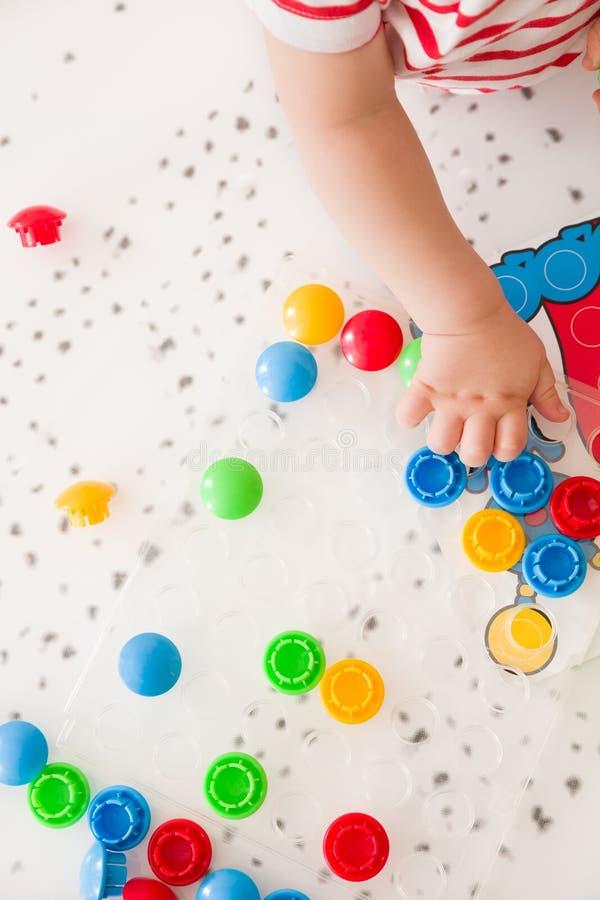 Zbliżenie dziecka ` s ręka bierze jaskrawą mozaikę rozdziela Bawić się kolor w domu i uczący się Odgórny widok zdjęcie stock