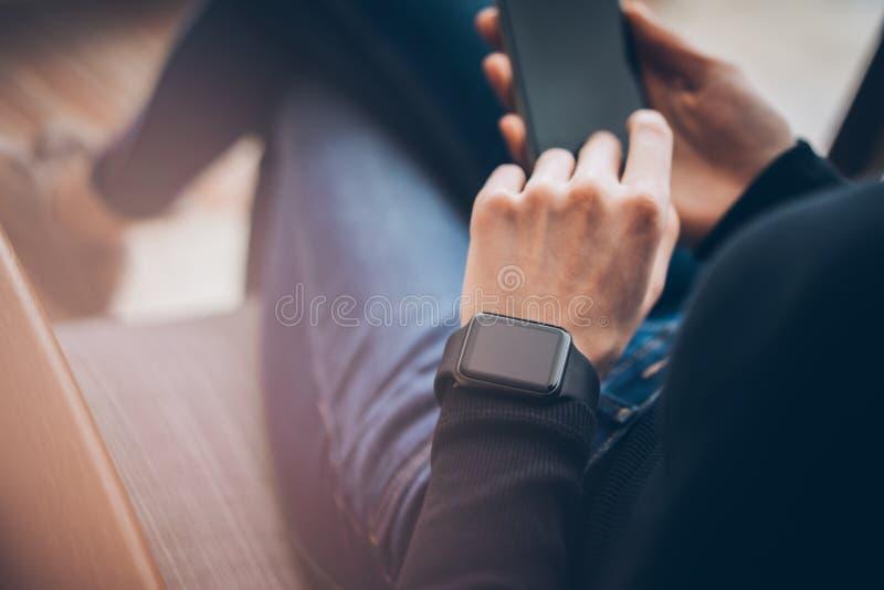 Zbliżenie fotografia żeńskie ręki dotyka parawanowego smartphone i jest ubranym rodzajowego projekta mądrze zegarek Filmów skutki zdjęcie royalty free