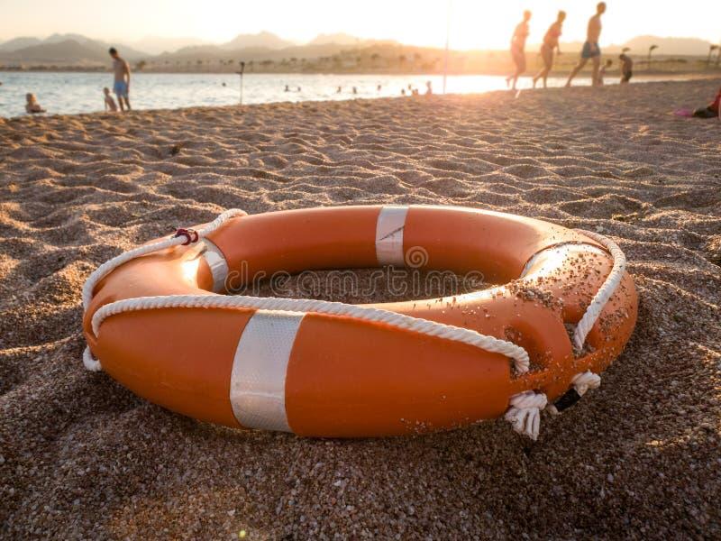 Zbliżenie fotografia czerwony plastikowy życia oszczędzania pierścionek na piasku denna plaża przeciw pięknemu zmierzchowi nad oc fotografia royalty free