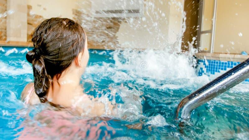 Zbli?enie fotografia dwa nastoletniej dziewczyny bawi? si? wod? i bryzga przy basenem zdjęcie royalty free