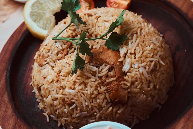 Zbli?enie fotografia indyjski tradycyjny naczynie z ry?, cytryn?, warzywami i kolendrowym li?ciem, obraz stock