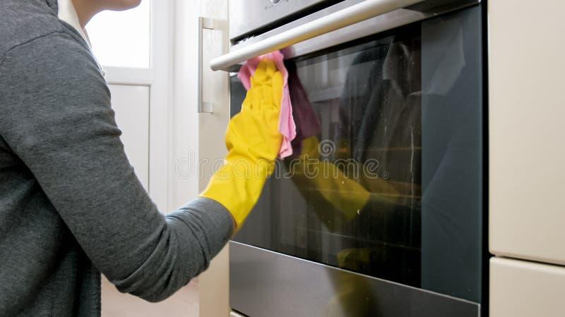 Zbliżenie fotografia młoda kobieta w myje brudnego witrażu piekarnika drzwi z żółtymi rękawiczkami zdjęcie royalty free