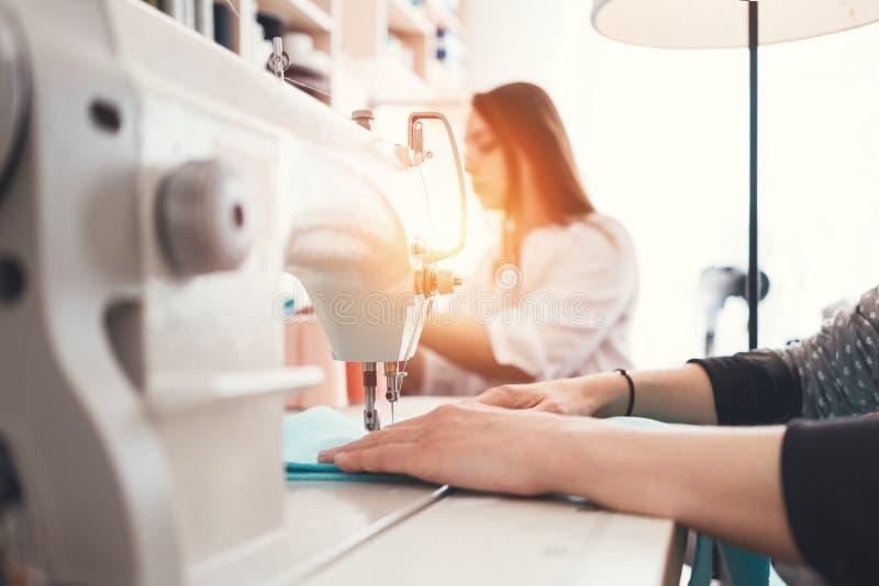 Zbliżenie fotografia młodej kobiety ` s wręcza szwaczki obsiadanie i szy na szwalnej maszynie w kreatywnie projektanta studiu zdjęcie stock