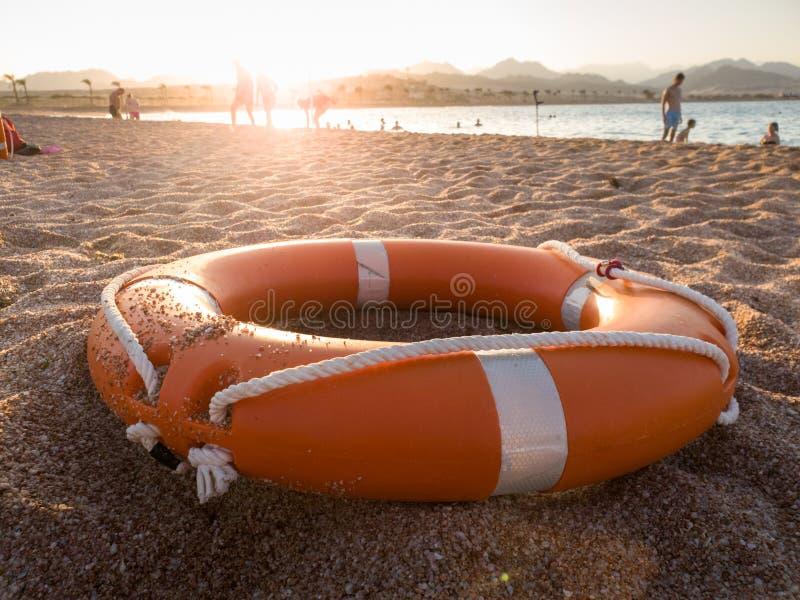 Zbliżenie fotografia pomarańczowy klingerytu pierścionek dla ratować tonięć ludzi na dennym lying on the beach na plaży fotografia stock
