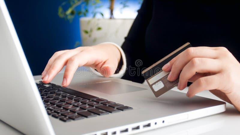 Zbliżenie fotografia pracuje na laptop pisać na maszynie liczbie jej kredytowa karta młoda kobieta obraz royalty free