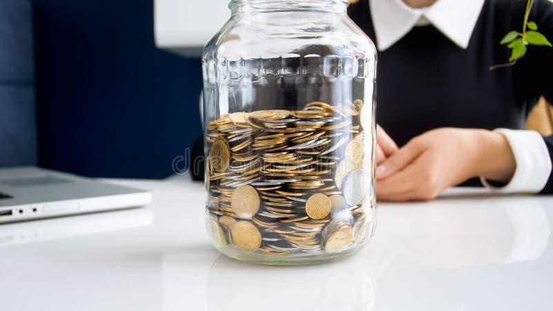 Zbliżenie fotografia szklany słój pełno monety na biurowym biurku zdjęcia stock