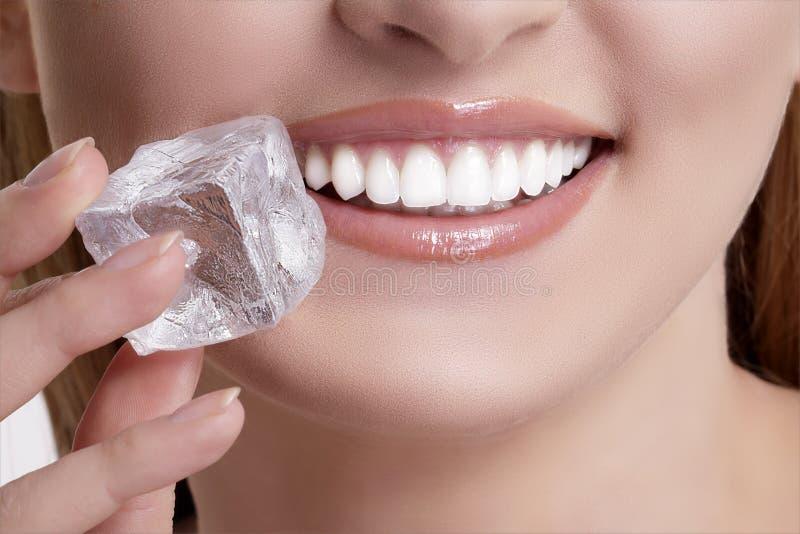 Zbliżenie gryźć kostkę lodu piękna kobieta obraz royalty free