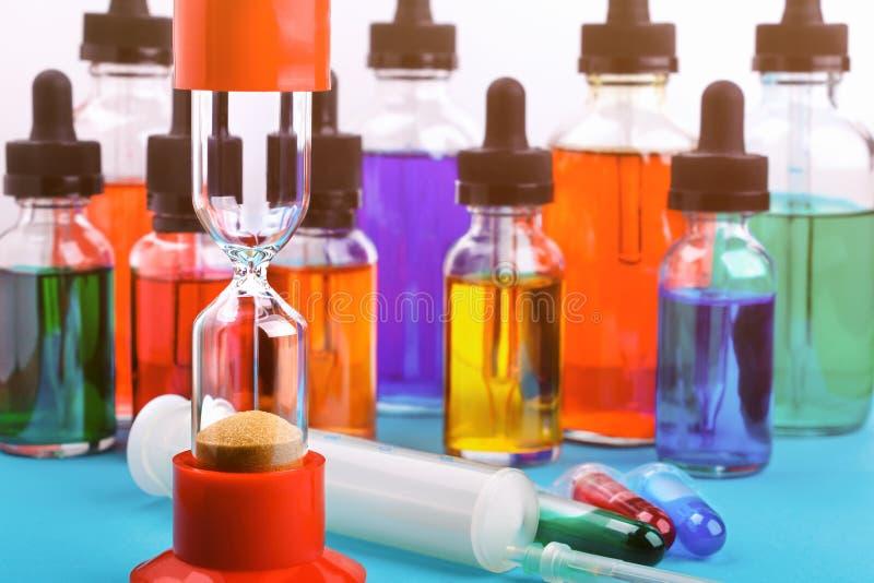 Zbliżenie hourglass na błękit powierzchni i tło z szklanych butelek wypełniającym barwiącym cieczem i strzykawką obraz royalty free