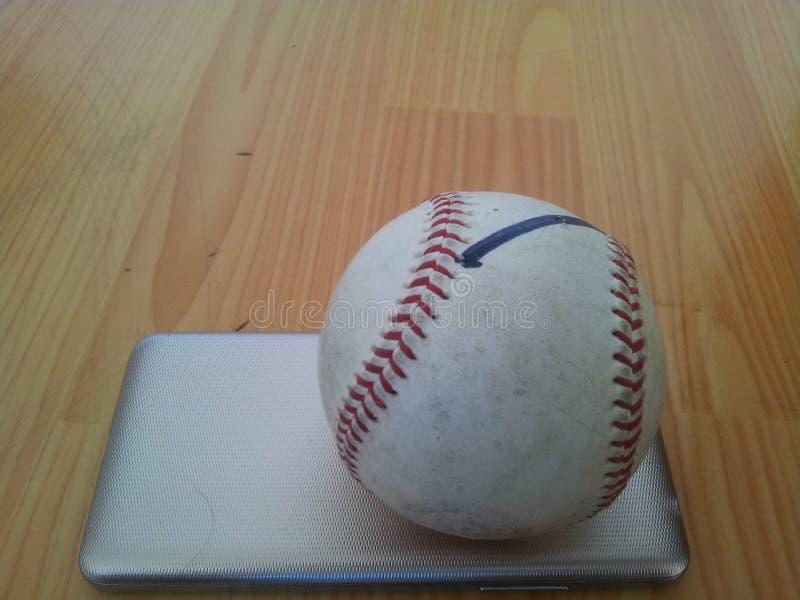 Zbliżenie i Odgórny widok białego krykieta ciężka piłka nad mądrze telefonem na drewnianej podłoga zdjęcie royalty free