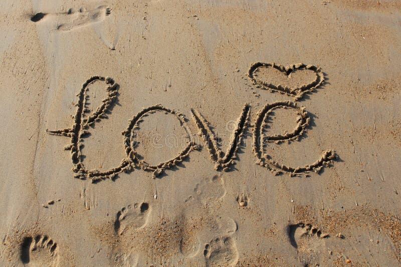 Zbliżenie inskrypcja, symbol serce i odciski stopi w piasku «miłość «, zdjęcia royalty free