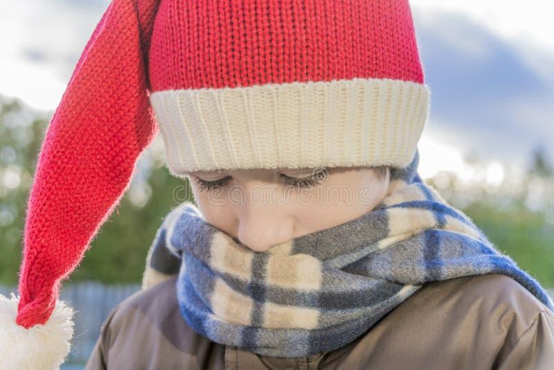 Zbliżenie jest ubranym Santa kapelusz chłopiec, twarz zakopująca w szaliku fotografia royalty free