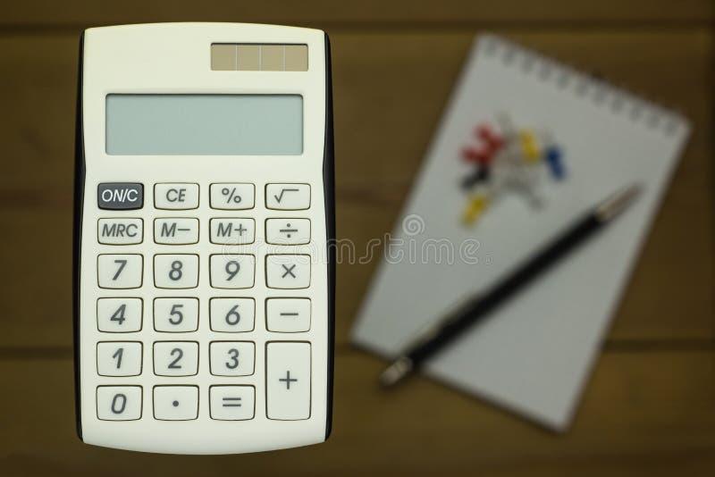 Zbliżenie kalkulatorzy na drewnianym tle z notatnikiem fotografia stock