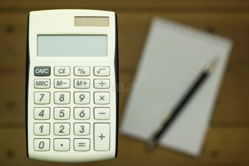 Zbliżenie kalkulatorzy na drewnianym tle z notatnikiem zdjęcia stock