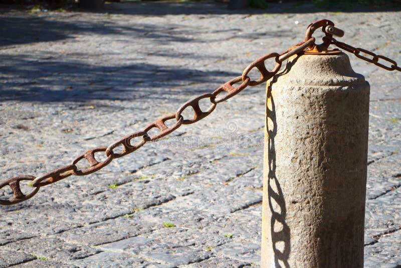 Zbliżenie kamienny płotowy łańcuch na kamiennym bruku tle i filar zdjęcie stock