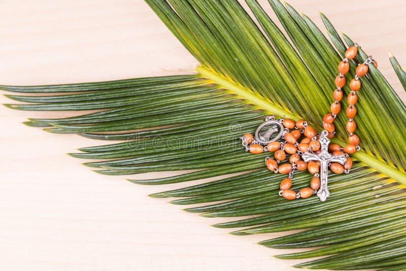 Zbliżenie Katolicki różaniec z krucyfiksem i koraliki na palmowym liściu obraz royalty free