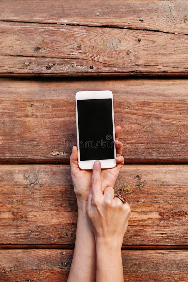 Zbliżenie kobiet ręki Trzyma Nowożytnego Smartphone Na Różowym tle obraz stock