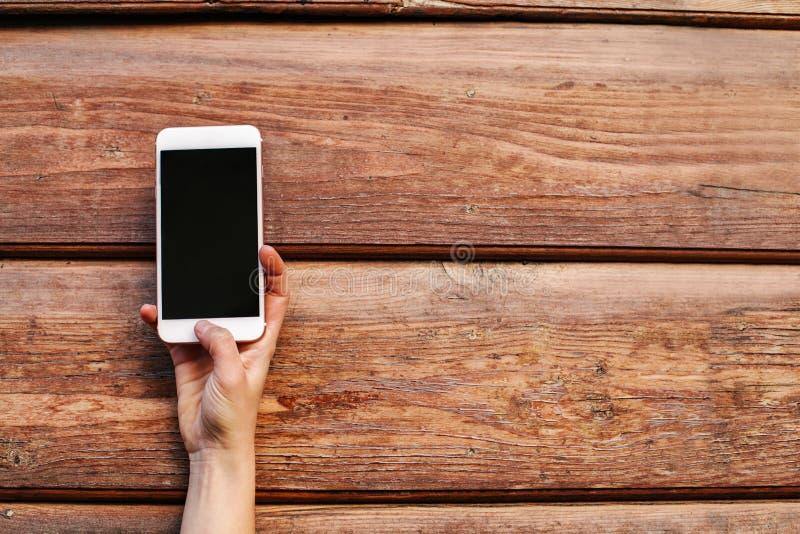 Zbliżenie kobiet ręki Trzyma Nowożytnego Smartphone Na Różowym tle obrazy stock