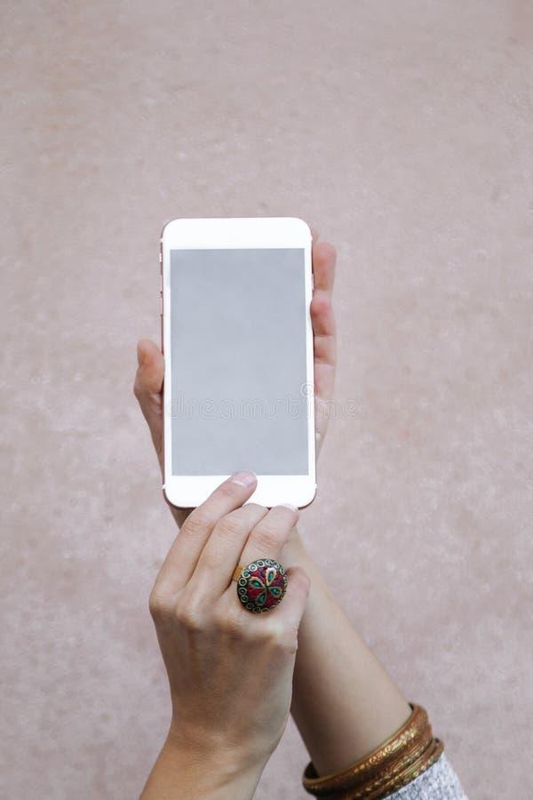 Zbliżenie kobiet ręki Trzyma Nowożytnego Smartphone Na Różowym tle zdjęcia royalty free